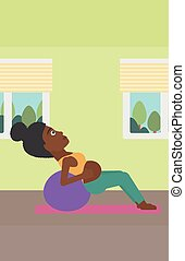 Pregnant woman on gymnastic ball. - An african-american...