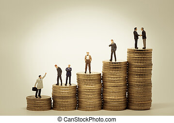 Various people standing on stacks of coins