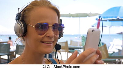 Close-up of young woman in headphones talking over phone -...
