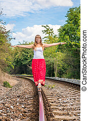 Young lady walking on railway tracks - Young lady in red...