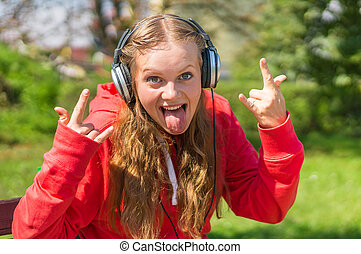 Young lady listening to music and relaxing on a park bench