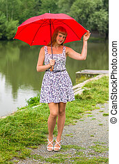 Young lady with red umbrella near the pond - Beautiful young...