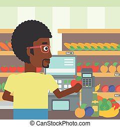 Cashier standing at the checkout in supermarket - An...