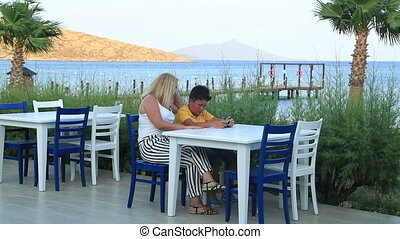 Mother and son with smart phone - Mother and son sitting...