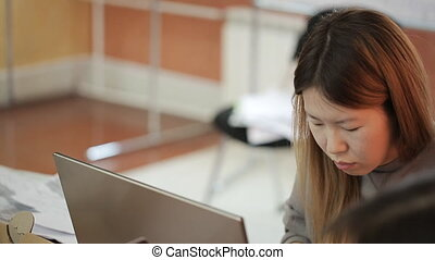 Chinese woman works on personal computer in office.