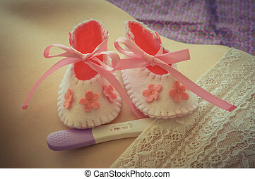 Newborn baby girl booties and pregnancy test on belly