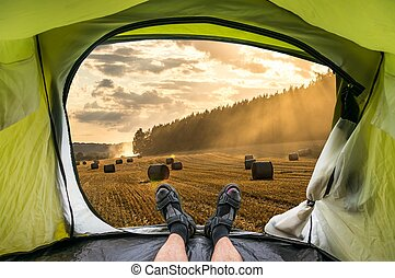 View from inside a tent on the sunset and wheat field