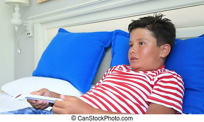 Child watching television - Child lying on a bed and...