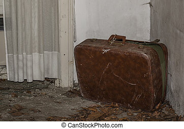 old suitcase in a corner of abandoned house