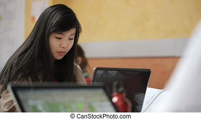 Pretty chinese woman works on personal computer in studio....