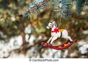 Rocking horse and snowy pine tree decorated for Christmas...