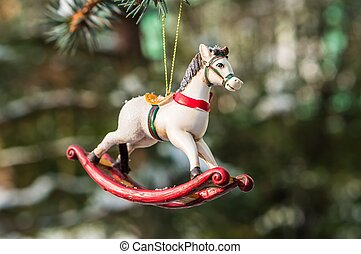 Rocking horse, closeup of Christmas tree decoration on snowy...