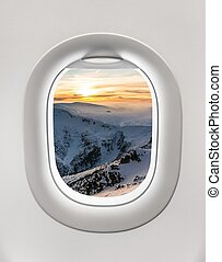 Looking out the window of a plane to the winter mountains...