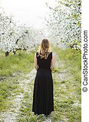 Beautiful young woman in spring garden backview - Beautiful...