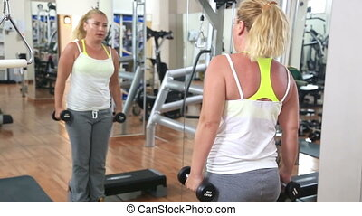 Woman Exercising In The Gym - Blonde woman with dumbbells...