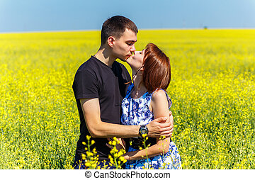 Image of happy couple kissing in yellow meadow at summer