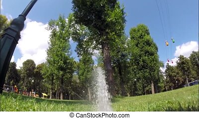 Watering grass in the park - Jet of water hits out of the...