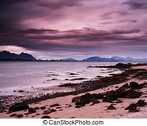 Horizontal pink vibrant evening at Norway fjords beach...