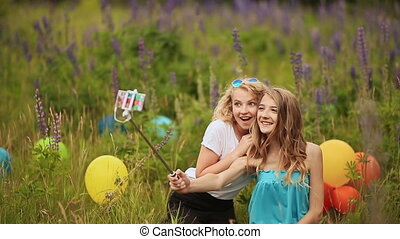 Two young pretty girls make selfie. Students are sitting on the lawn in the park. Self-portrait. Shooting on the phone. Selfie stick.