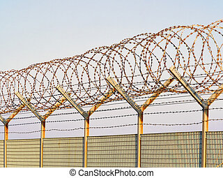 Concertina razor wire and barbed wire on a metal fence -...