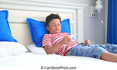 Child with remote controller lying on a bed and sleeping