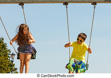 Two children having fun on swingset - Fun and joy of...