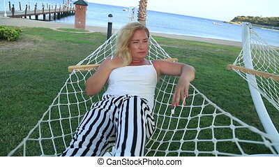 Woman relaxing in a hammock near the sea