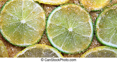 slices of limes and lemons mixed with cane sugar - view on...