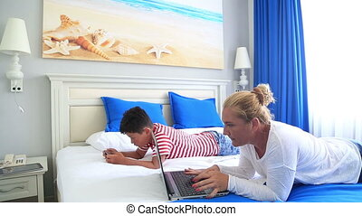 Mother and son browsing internet in a laptop and smart phone...