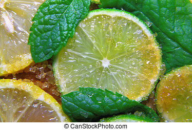 slices of limes and lemons, leaves of mint and cane sugar -...