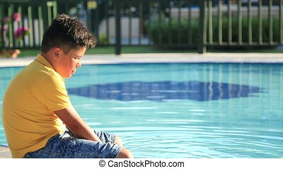 Happy child at summer holiday sitting near the pool
