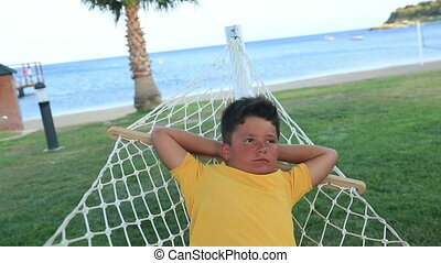 Young boy  relaxing in a hammock