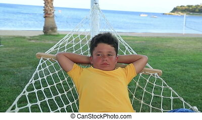 Young boy  relaxing in a hammock near the sea