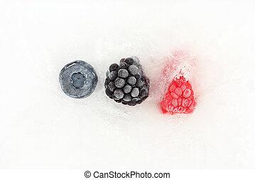 blueberries, blackberries and raspberries frozen in ice
