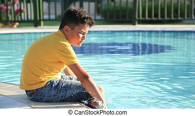 Young boy sitting near the pool