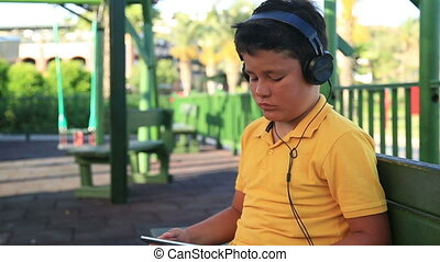 Child using digital tablet - Young boy with earphone using...