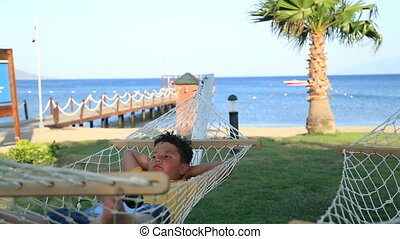 Young boy sleeping on a hammock