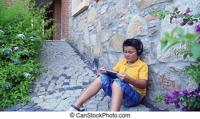 Young boy with  earphone using digital tablet outdoor