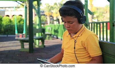 Young boy with earphone - Young boy with earphone using...