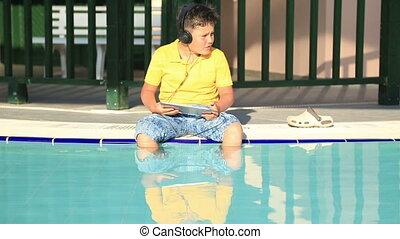 Young boy with  earphone using digital tablet near the pool