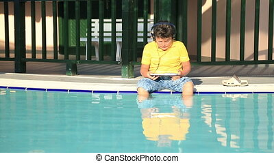 Boy using digital tablet - Young boy with earphone using...