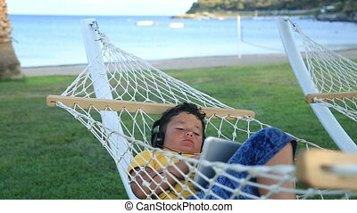 Young boy with earphone using i pad in a hammock