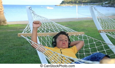 Young boy with earphone listening to music in a hammock