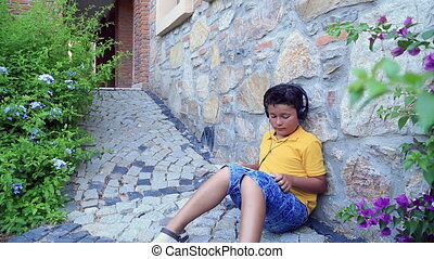 Child using digital tablet outdoor - Young boy with earphone...