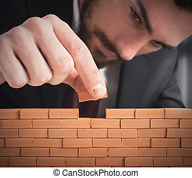 Build the business - Businessman building a wall with small...