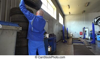 Stack of tires and male mechanic take one. Seasonal car tire...