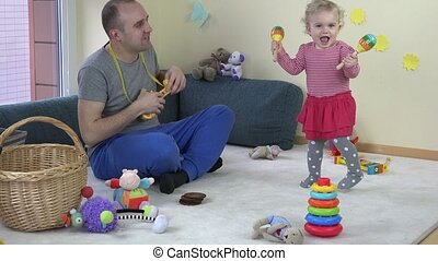 Father play toy guitar and baby daughter shake rattle Family...