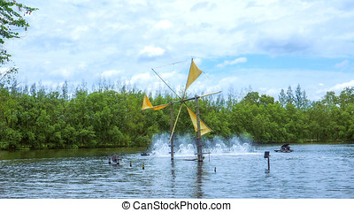 Natural Energy Wind turbines baler and fountain in lake...