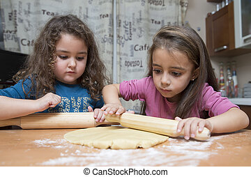Girls cooking - Two beautiful kids cooking dough with...