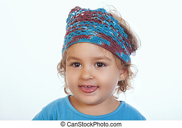 Lovely kid in blue knit headband sticking out tongue -...